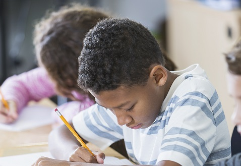 Elementary-age children in a classroom with pencil and paper taking a test.