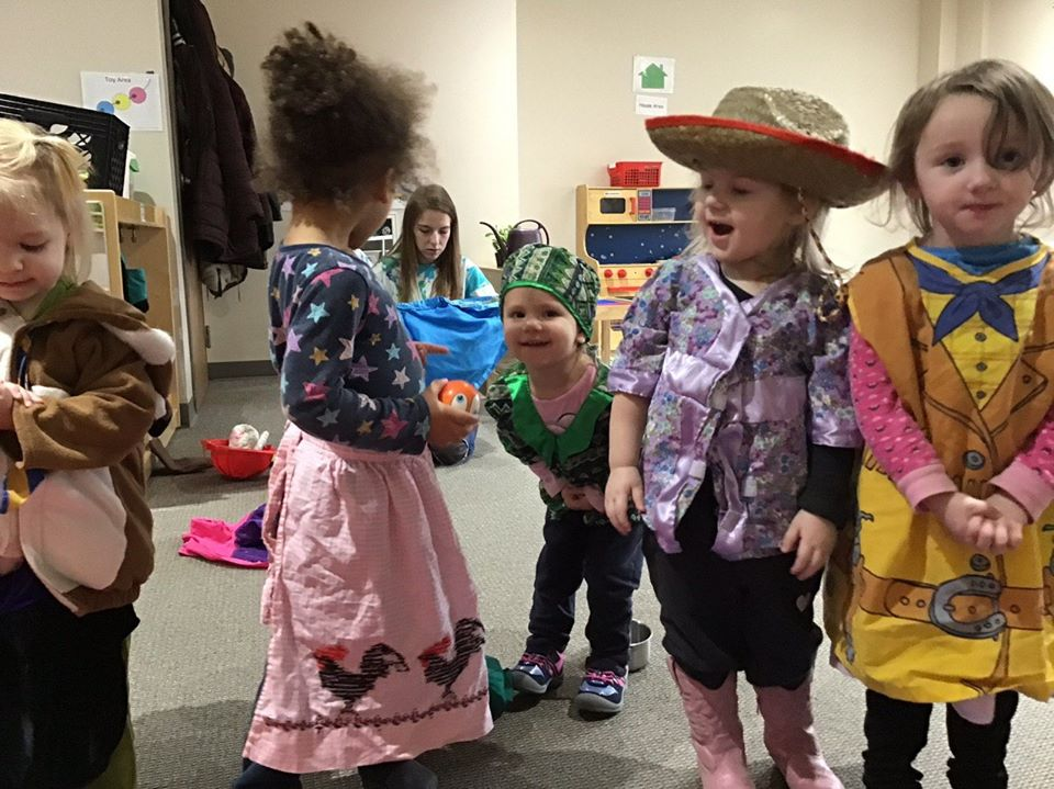 Group of children playing dress-up in a classroom at the learning center.